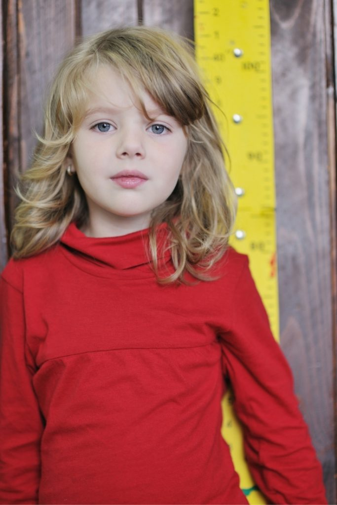 young girl in red shirt staring at the camera