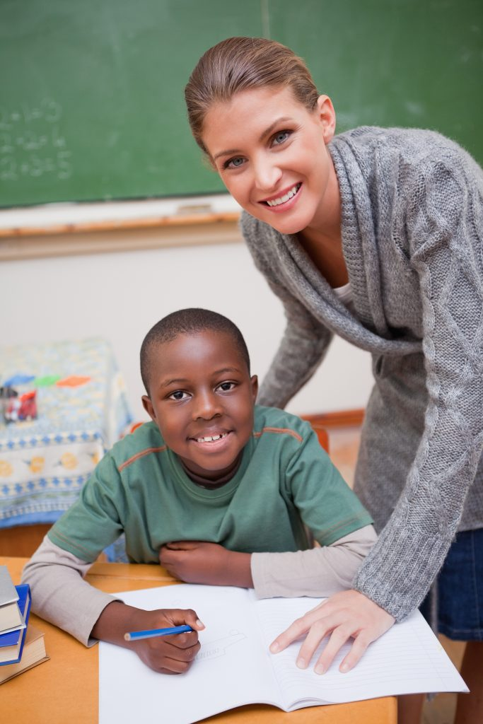 Portrait of a teacher explaining something to a smiling schoolboy in a classroom