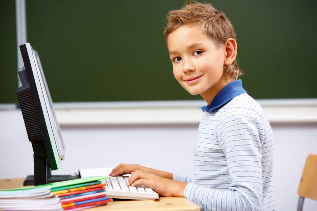 boy typing on computer with head turned looking at camera
