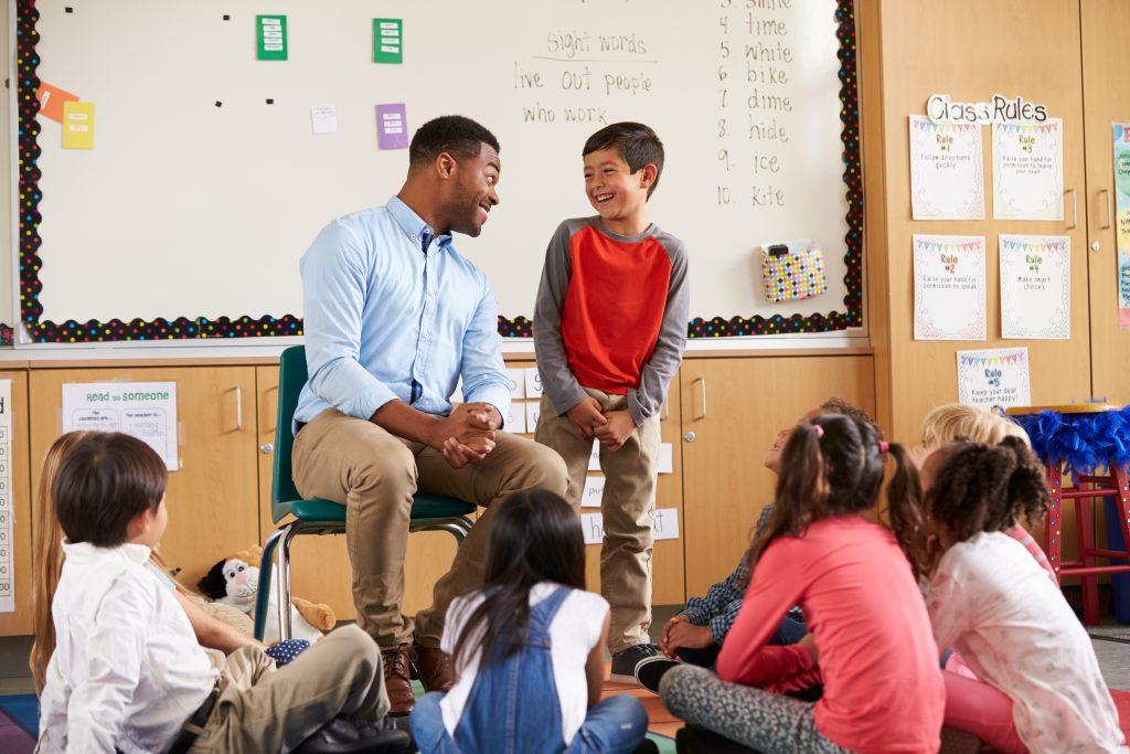 Schoolboy at front of elementary class talking with teacher