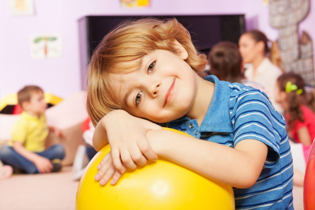kindergarten boy hugging a yellow ball