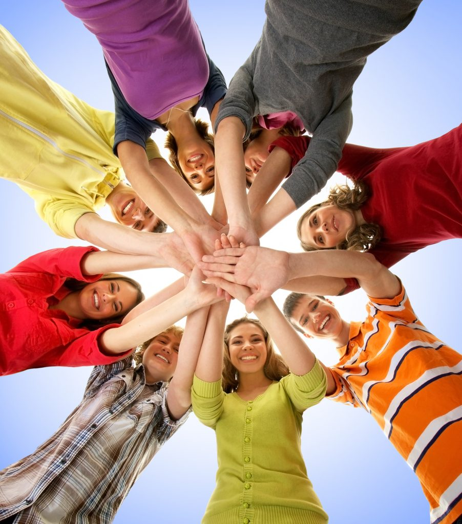 group of eight teenagers in a circle  with hands touching in the middle