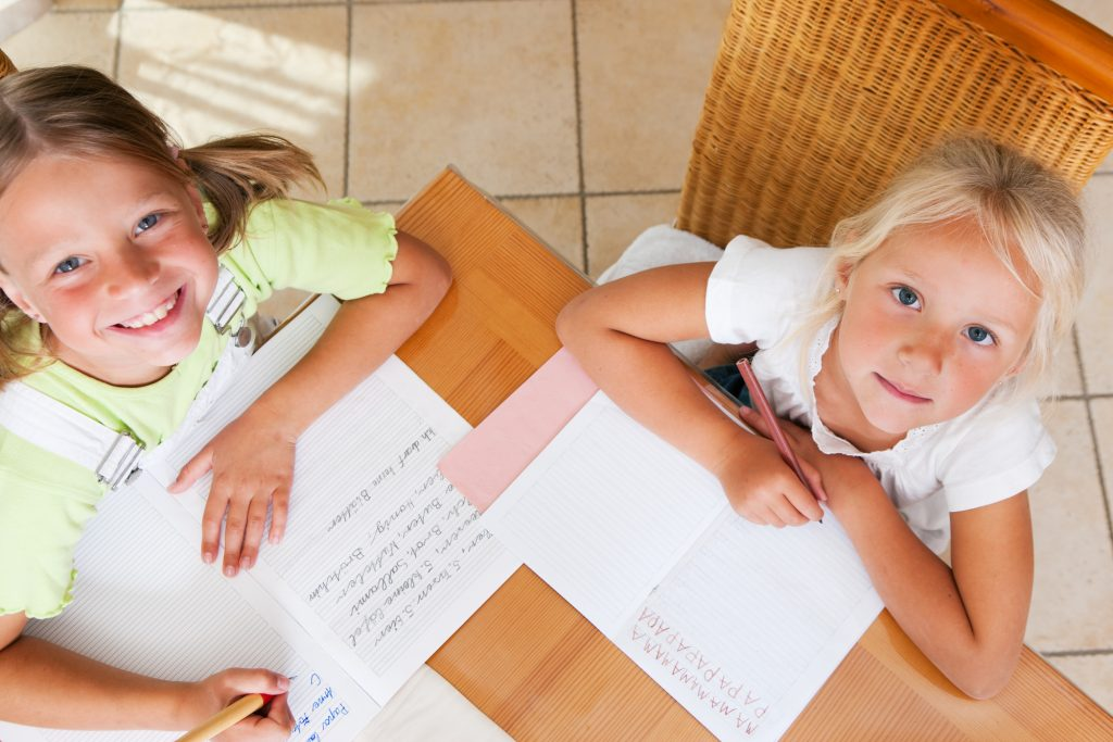 two girls doing handwriting looking up and smiling