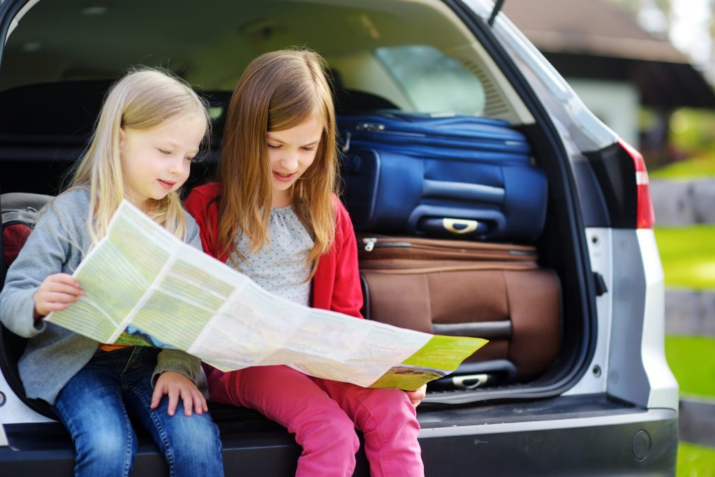 Two girls in back of car reading map