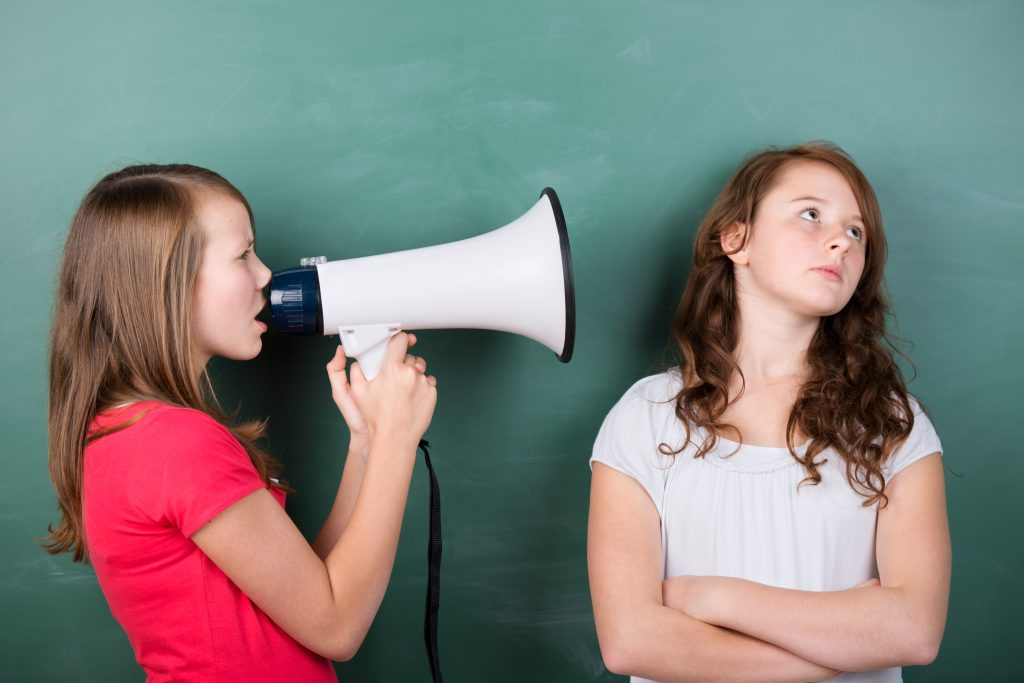Teen girl using megaphone with another teen girl looking away