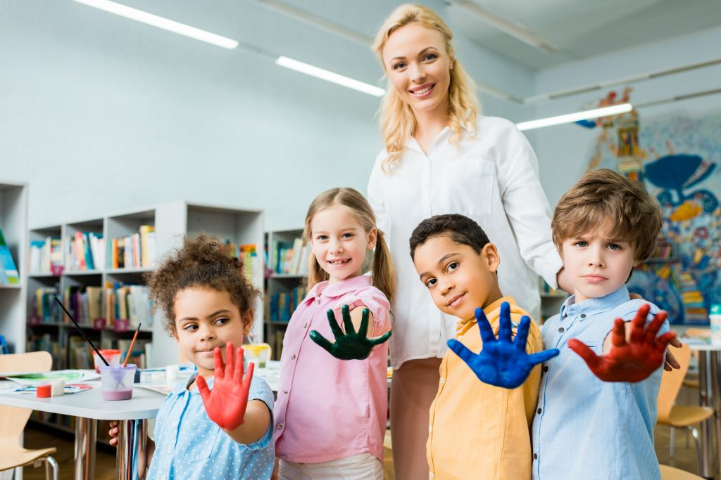 female teacher with four young students with pain on their hands