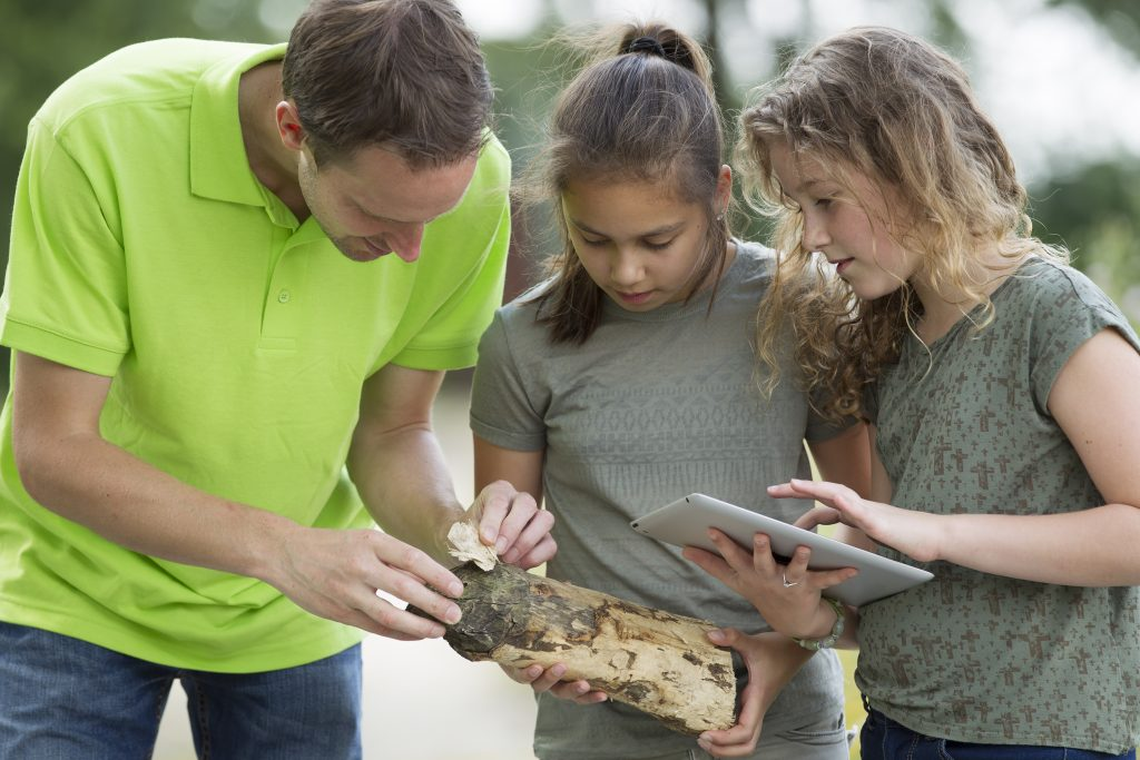 male teacher with two preteens doing outside science activity