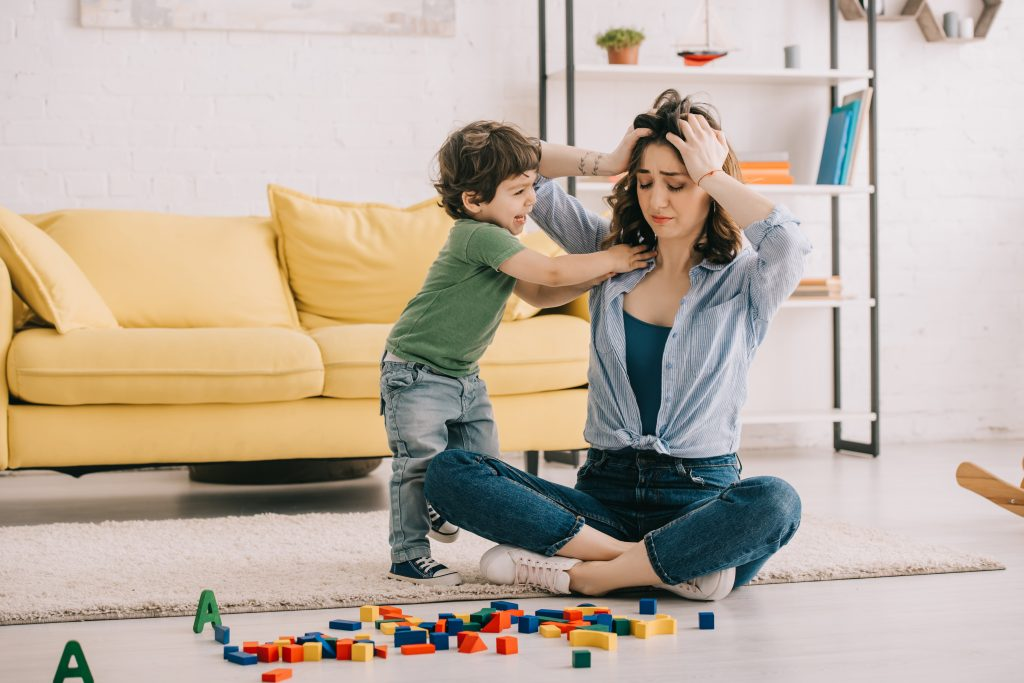 Mom looking stressed out with toddler and building blocks