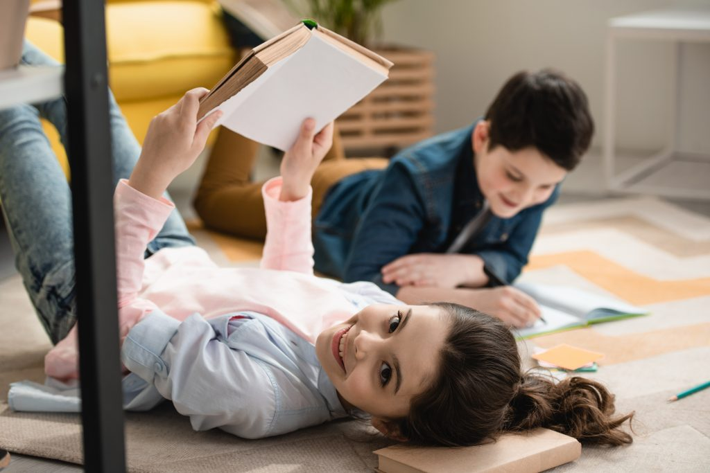 Girl reading book and boy working on writing inside of home