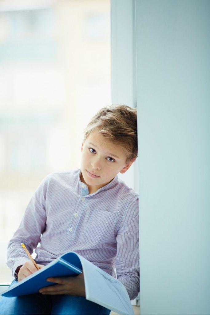 Boy writing in journal