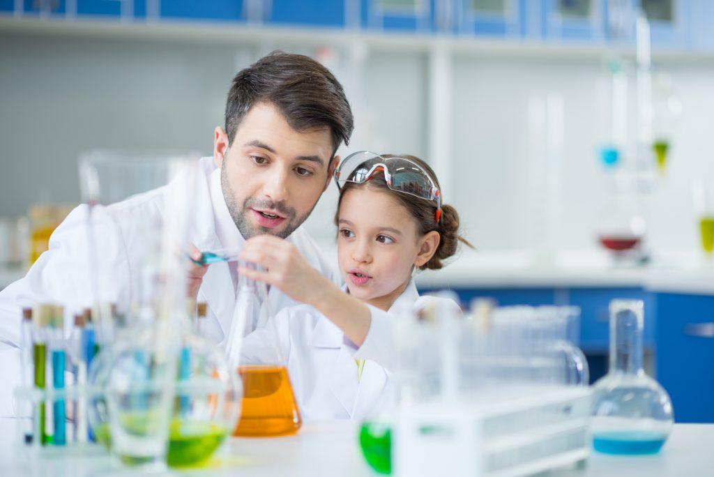 girl and male teacher doing chemistry