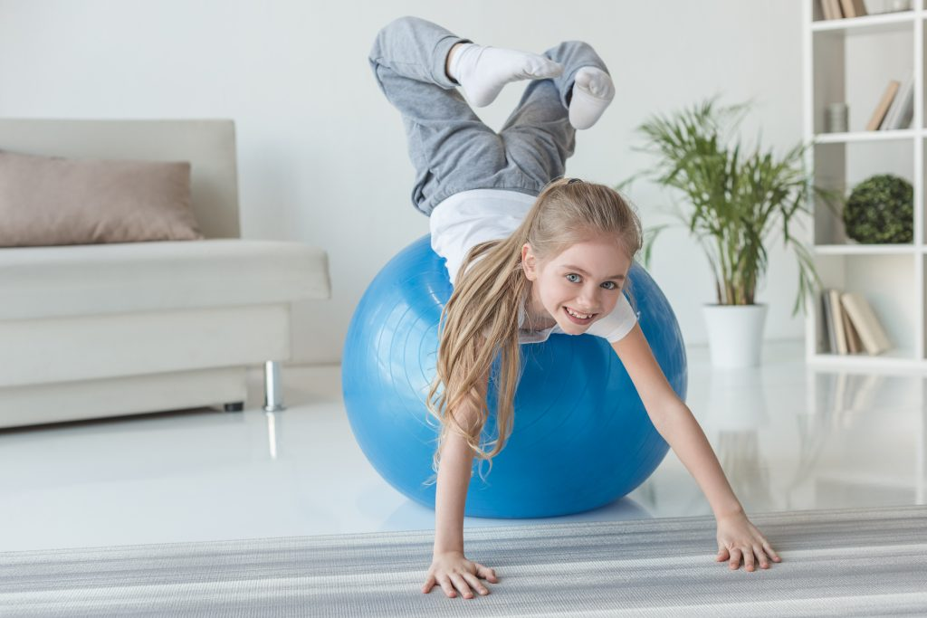 young girl on blue exercise ball
