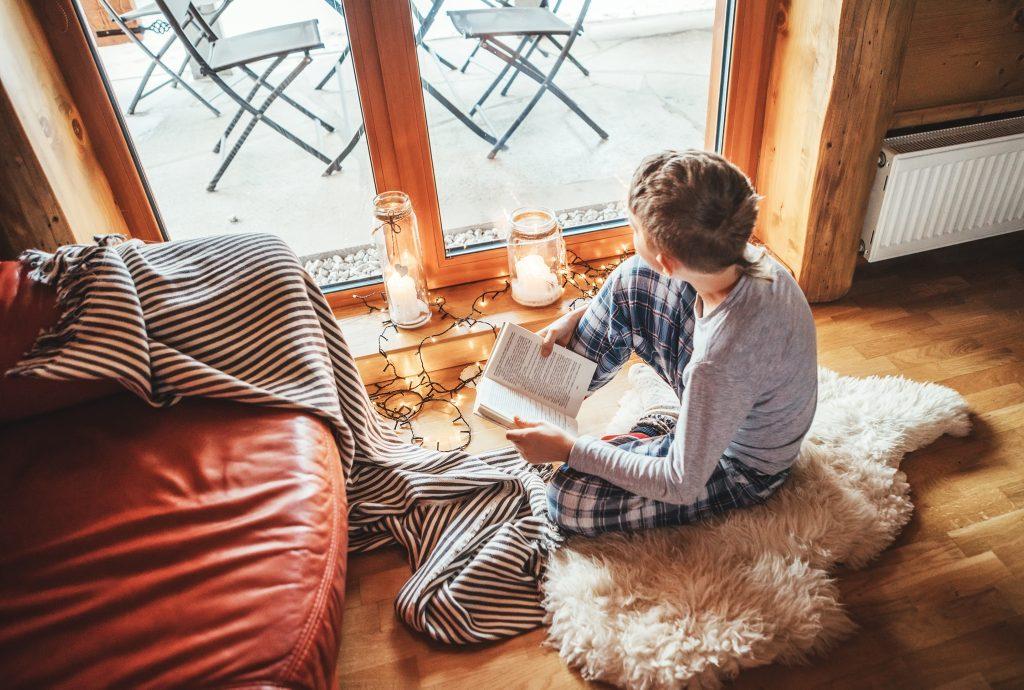 boy reading in cozy environment in pajamas
