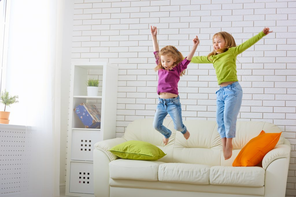 Young girls jumping on couch