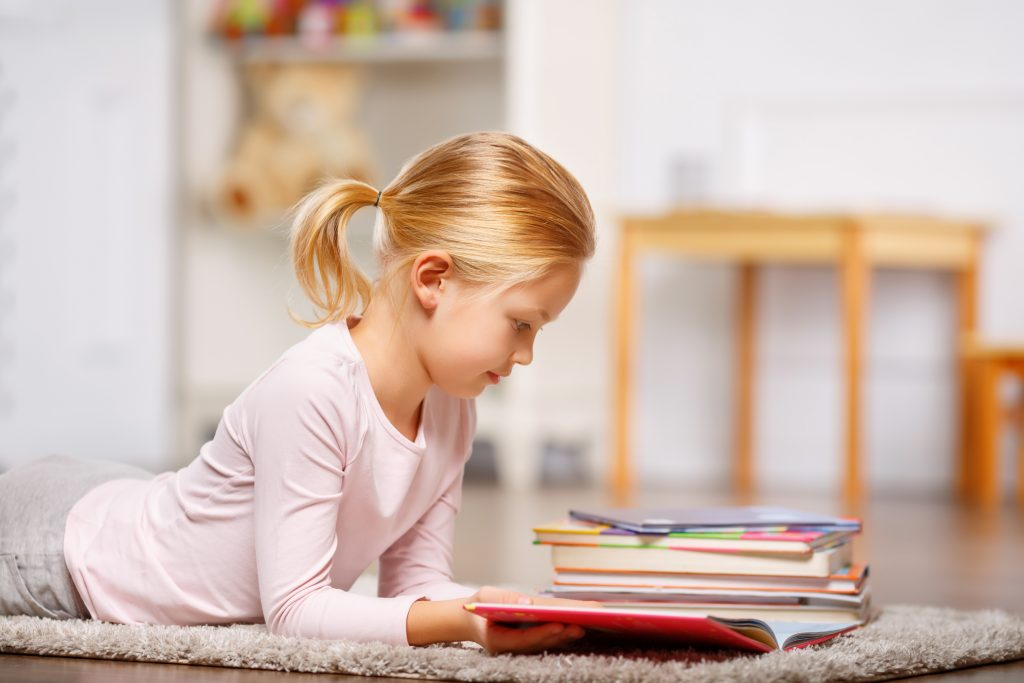 Blonde girl lying on carpet reading from stack of books